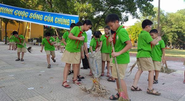 Các em học sinh tiểu học vệ sinh vườn trường